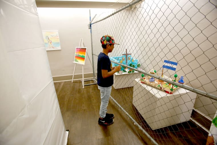 """Some exhibits at \""""Uncaged Art\"""" are behind chain-link fencing, to suggest the conditions at the Tornillo detention center."""