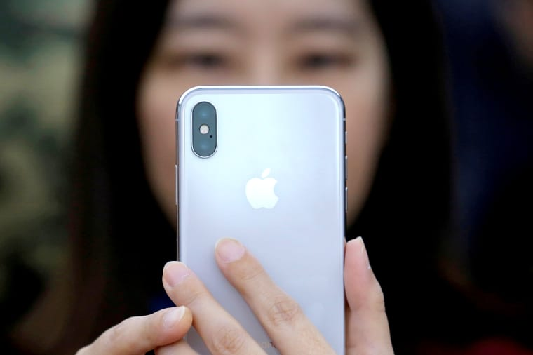 Image: FILE PHOTO: A attendee uses a new iPhone X during a presentation for the media in Beijing