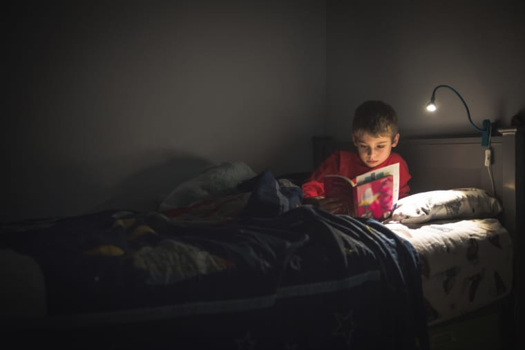 Image: Boy reading in bed