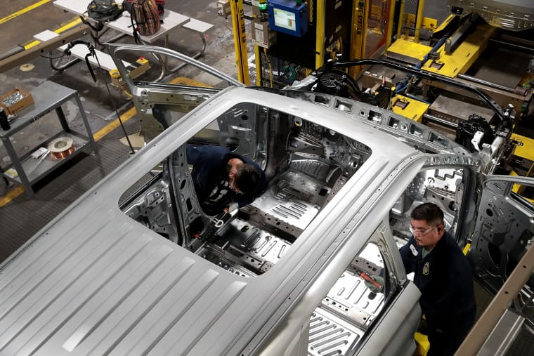Image: Workers assemble Ford vehicles at an assembly plant in Chicago on June 24, 2019.