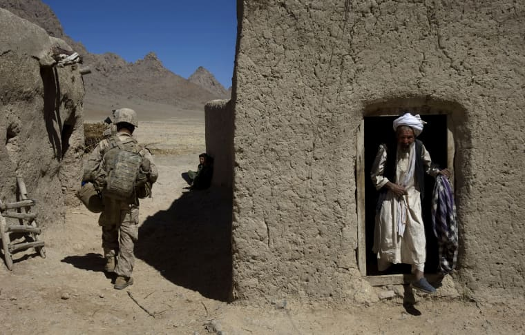 Image: An Afghan man steps out of his house