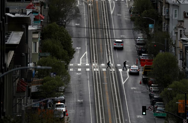 Image: Two pedestrians cross an empty California Street on March 16, 2020 in San Francisco.