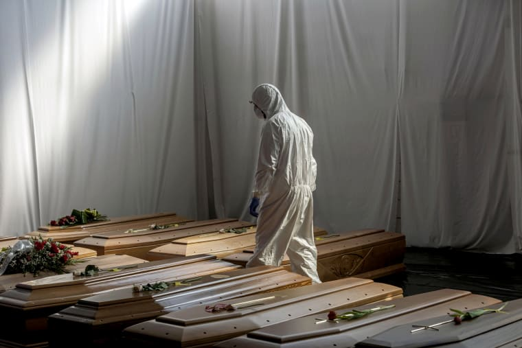 Image: The coffins of people who died from coronavirus wait to be transported from Bergamo to Florence for cremation on April 7, 2020.