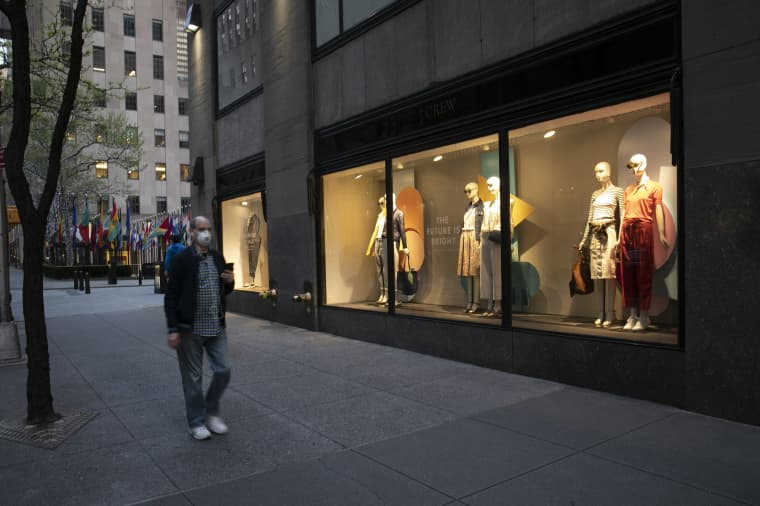 Image: A man wearing a mask walks by a window display at a J Crew store in Rockefeller Center