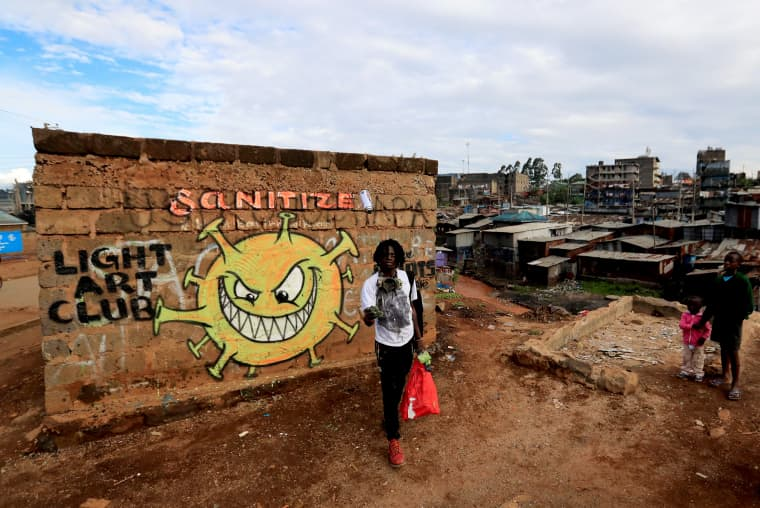 Image: Brian Musasia Wanyande, an artist from the Mathare Roots's youth group, walks after painting an advocacy graffiti against the spread of the coronavirus disease (COVID-19), at the Mathare Valley slum, in Nairobi
