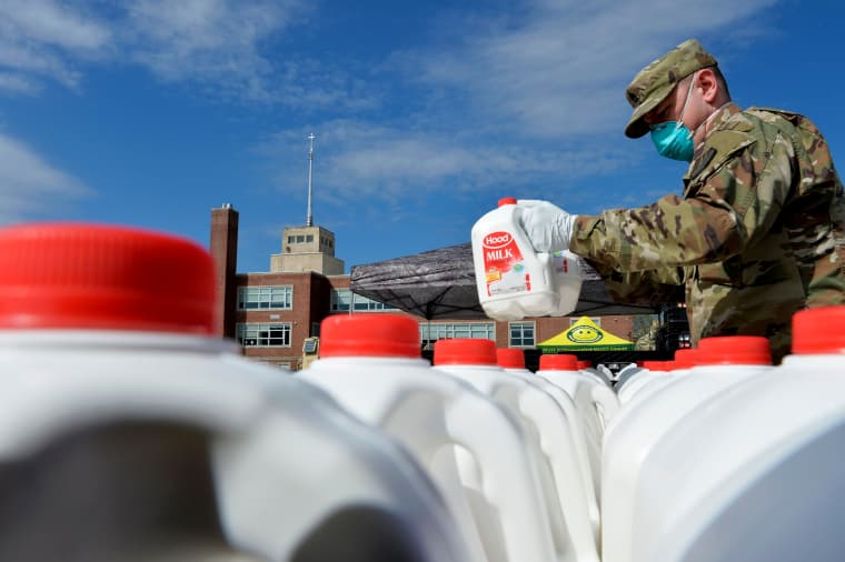 Image: Massachusetts National Guard soldiers distribute milk to residents in need in Boston on May 7, 2020. The milk was provided by dairy farmers getting rid of excess milk after demand fell during the coronavirus outbreak.