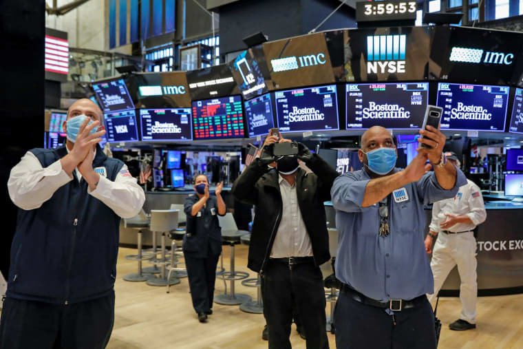 Image: Workers celebrate the during closing bell, as they prepare for the return to trading, on the floor at the NYSE in New York