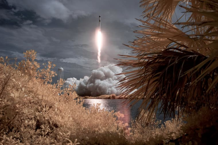 Image: A SpaceX Falcon 9 rocket carrying the Crew Dragon spacecraft launches from NASA's Kennedy Space Center in Cape Canaveral, Fla., in this false color infrared exposure photo on May 30, 2020.
