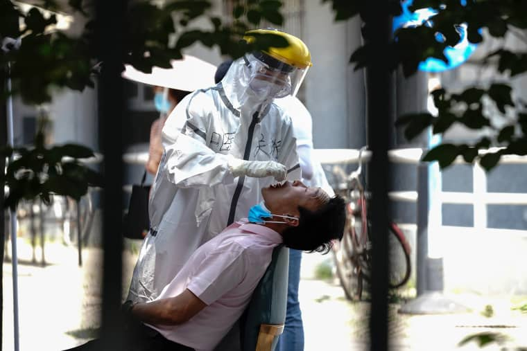 Image: A nurse wearing a protective suit and mask takes a nucleic acid test for COVID-19 from a person who either visited or lives near the Xinfadi Market at a testing facility at a Sport Center on June 16, 2020 in Beijing, China.