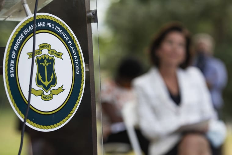 """Image: The seal of the State of Rhode Island decorates a podium as Gov. Gina Raimondo looks on at right during a news conference where she announced that she has signed an executive order to remove the phrase \""""Providence Plantations\"""" in the state's formal"""