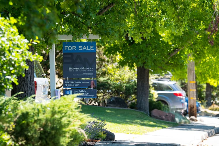 """A \""""For Sale\"""" sign stands in front of a single family home in San Rafael"""