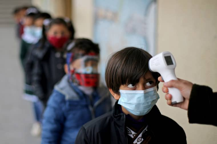 Image: A Palestinian student has his temperature checked as he enters his reopened school in the southern Gaza Strip