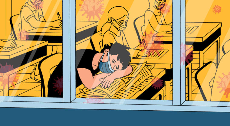 Image: Illustration, seen from outside of school windows, of a student with his head down on a messy desk while wearing a mask, looking forlorn. Other students in masks work at their desks. Coronavirus spores reflect in the windows.