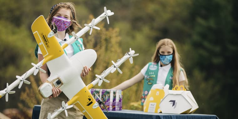 Girl Scouts Alice Goerlich, right, and Gracie Walker pose with a Wing delivery drone in Christiansburg, Va. The company is testing drone delivery of Girl Scout cookies in the area.