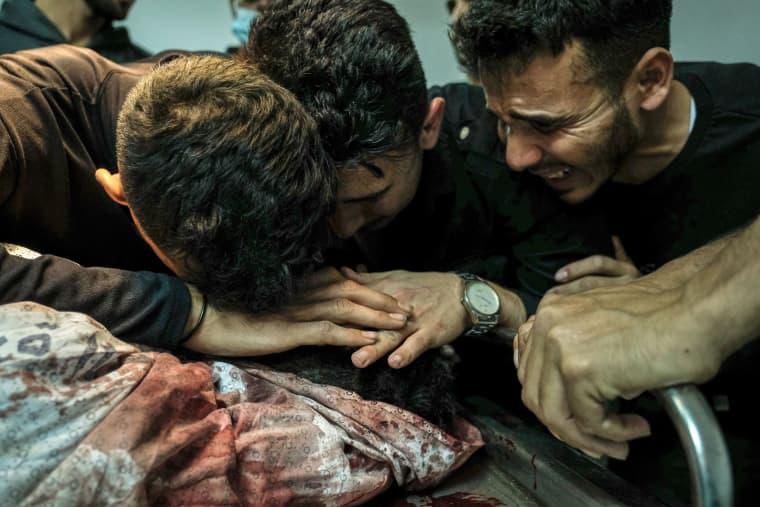 Image: Relatives of Palestinian Izz al-Deen Helles during his bid farewell at Al-Shifa Hospital