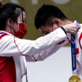 Olympic athletes help each other don their medals