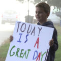 Boy cheers passing motorists from his driveway with 'happy signs'