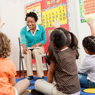 Image: Teacher and children sitting on floors with hands raised