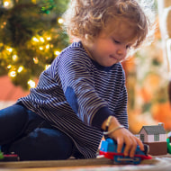 Caucasian baby boy playing with toys near Christmas tree