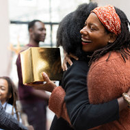 Happy mother and daughter with Christmas gift hugging