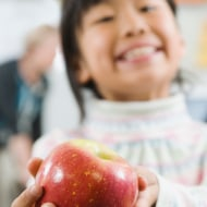 Elementary student holding an apple in her hand
