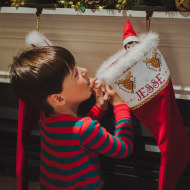 Side view of curious boy looking at toy in sock hanging by fireplace during Christmas