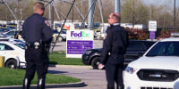 Police stand near the scene where multiple people were shot at the FedEx Ground facility in Indianapolis on April 16, 2021.