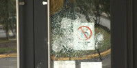 The door to a synagogue is damaged after a person through a rock at it in the Bronx borough of New York.