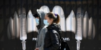 "Image: People wearing masks walk by a banner showing syringes as vampire fangs during the vaccination marathon organized at the ""Bran Castle\"" in Bran village, Romania, on May 8, 2021."