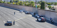 Image: Yellow crime scene tape stretches across the northbound lanes of the 55 freeway as police investigators walk the freeway looking for evidence following a shooting on May 21, 2021 in Orange, Calif.