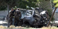 Image: Afghan security forces inspect the wreckage of a passenger van after a blast in Kabul, Afghanistan