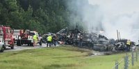 Emergency personnel work at the accident site as smoke rises from the wreckage after about 18 vehicles slammed together on a rain-drenched Alabama highway during Tropical Storm Claudette in Butler County on June 19, 2021.