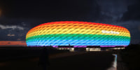 Image: The outside of the soccer stadium Allianz Arena which is illuminated in rainbow colors