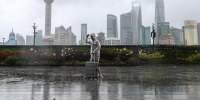Image: Man walks in the rain on The Bund as Typhoon In-fa approaches Shanghai