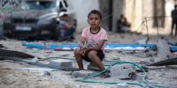Image: A Palestinian boy sits looking at others inspecting the damage of their shops after Israeli airstrikes on Jabaliya refugee camp, northern Gaza Strip, on May 20.