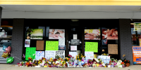 Image: Flowers, candles and signs lie at a makeshift memorial outside Young's Asian Massage following the deadly shootings in Acworth, Ga., on March 19, 2021.