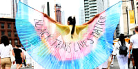 """A protestor wearing \""""Black Trans Lives Matter\"""" wings marches during the \""""Brooklyn Liberation: An action for Trans Youth March\"""" on June 13, 2021, in New York."""