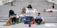 Rep. Cori Bush, D-Mo., center, joined by Congressional staffers and activists, protests the expiration of the eviction moratorium outside the Capitol on July 31, 2021.