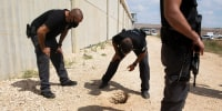 Police officers and prison guards inspect the scene of a prison escape outside the Gilboa prison in northern Israel on Sept. 6, 2021.