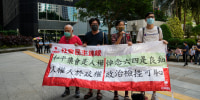 """Pro-democracy activists outside a court in Hong Kong, Wednesday, Sept. 15, 2021, where nine people were handed jail sentences of up to 10 months over their roles in last year's banned Tiananmen candlelight vigil. The banner reads """"Peaceful assembly is a human right, mourning the victims of June 4th is a conscience."""" (AP Photo/Kin Cheung)"""