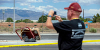 A passerby takes photos of the basket of the fatal balloon crash lying on the pavement in Albuquerque, N.M., on June 26, 2021.