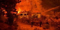 Firefighters work to control the Windy Fire as trees burn in the Sequoia National Forest near Johnsondale, Calif., on Sept. 22, 2021.