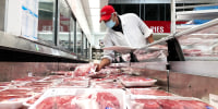 A butcher stocks a display case with packages of steaks at a Costco store on May 24, 2021, in Novato, Calif.