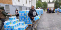 Image: A resident picks up bottled water at a distribution site, in Benton Harbor, Mich.