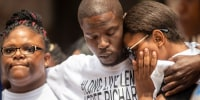 Image: Cheryl Frazier, sister of Leneal Frazier; Orlando Frazier, brother of Leneal; and Jamie Bradford, daughter of Leneal, embrace one another during a news conference outside of City Hall in Minneapolis on July 9, 2021.