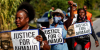 Image: People participate in a demonstration called by nonprofit organization Transformative Justice Coalition demanding justice for Ahmaud Arbery in Brunswick, Ga., on Oct. 22, 2021.