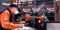 San Francisco Giants fans Dave Harding, center, and his wife, Nancy Faltisek, check in at one of the vaccination/negative test verification booths before being admitted to Oracle Park on April 9, 2021, in San Francisco.