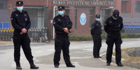 Security personnel gather near the entrance of the Wuhan Institute of Virology during a visit by the World Health Organization team in Wuhan in China's Hubei province on Feb. 3, 2021.
