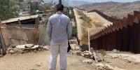 Un hombre de espaldas junto al muro fronterizo. Es Daniel, quien fue secuestrado, ahora espera una resolución de una solicitud de asilo en EE.UU. desde Tamaulipas, México.
