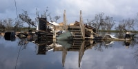 Image: A destroyed home in floodwater.